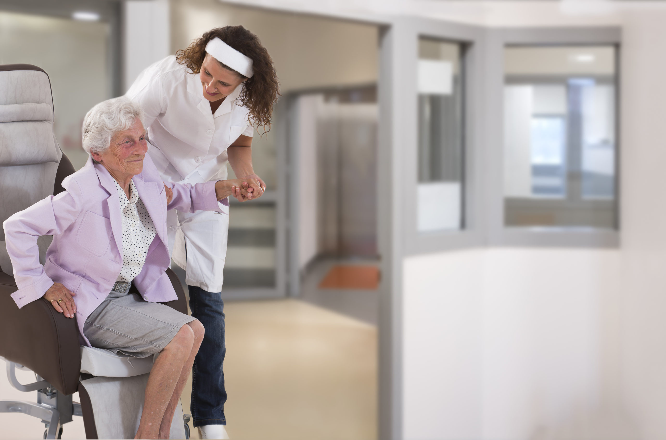 Nurse Helping Disabled Lady In Getting Up In Large, Windows, Background, Coridor
