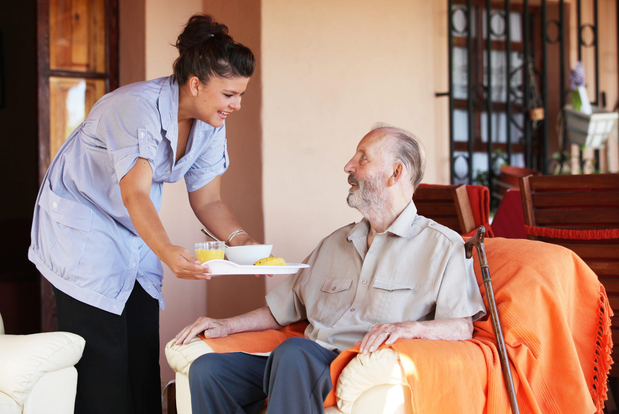 Elderly Senior Being Brought Meal By Carer Or Nurse