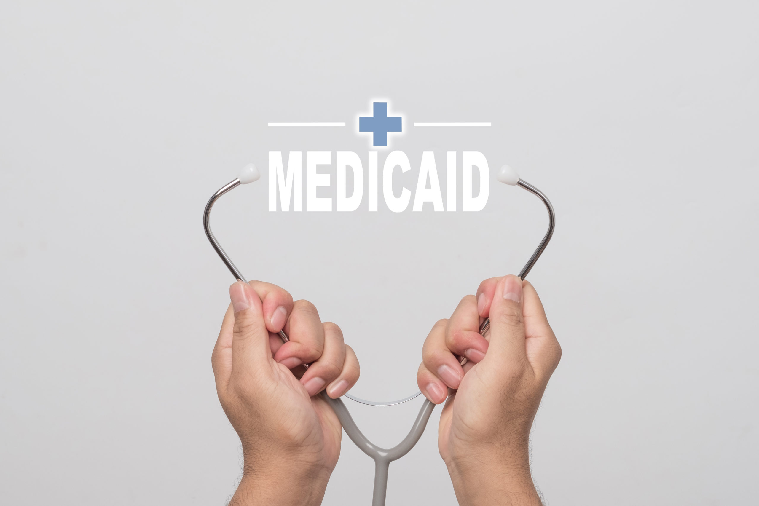 "Hands Holding A Stethoscope And Word ""medicaid"" Medical Concept."